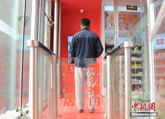 顾客通过手机扫码并通过人脸识别后进出超市。刘栋 摄