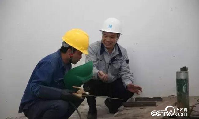 梁跃辉在指导焊工进行电焊操作