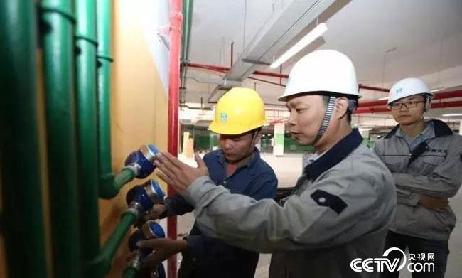 梁跃辉向工友讲解水表安装规范标准